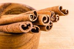 Zamyka up cynamon na drewnianym pucharze odizolowywającym na bielu Zdjęcie Royalty Free
