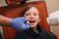 Zamyka up dentysta stawia intraoral osłonę i pomocniczą naczelnikostwa promieniowania rentgenowskiego maszynę dziecka cierpliwy u Zdjęcie Royalty Free