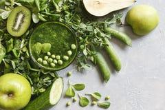 Zamyka up domowej roboty zielony smoothie z świeżym szpinakiem, grochami, ogórkiem, bonkretą i jabłkiem na szarym tle, Obrazy Stock