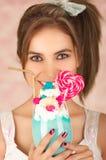 Zamyka up dosyć śliczna kobieta trzyma smakowitego błękitnego dojnego potrząśnięcie z cukierku sercem na wierzchołku, modny odzie Obraz Stock