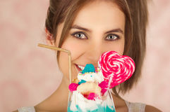 Zamyka up dosyć śliczna kobieta trzyma smakowitego błękitnego dojnego potrząśnięcie z cukierku sercem na wierzchołku, modny odzie Zdjęcia Stock