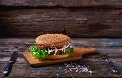 Zamyka Up hamburger Wypiętrzający Wysoko z Świeżymi polewami na Całej Zbożowej rzemieślnik babeczce na Nieociosanej Drewnianej po Obraz Stock