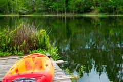 Zamyka up kajak na molu obok wielkiego zalesionego jeziora Zdjęcie Royalty Free