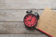 Zamyka up kalendarz, budzik i ołówek na stole, Fotografia Stock