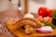 Zamyka up kiełbasy i pikantność z rozwidleniem nad a piec na grillu warzyw, pomidoru, czosnku, zielonego pieprzu, cebuli i rozmar Fotografia Stock