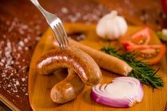 Zamyka up kiełbasy i pikantność z rozwidleniem nad a piec na grillu warzyw, pomidoru, czosnku, zielonego pieprzu, cebuli i rozmar Zdjęcie Stock
