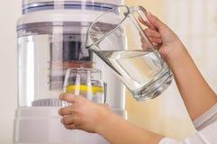 Zamyka up kobieta trzyma szkło woda w jeden ręce i miotaczu woda w jej innej ręce z filtrowym systemem, Zdjęcia Stock