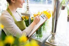 Zamyka up kobieta z schowkiem przy kwiatu sklepem Obraz Royalty Free