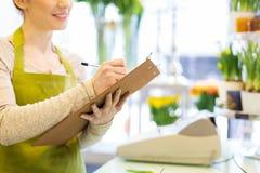 Zamyka up kobieta z schowkiem przy kwiatu sklepem Zdjęcia Stock