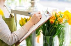 Zamyka up kobieta z schowkiem przy kwiatu sklepem Zdjęcie Stock
