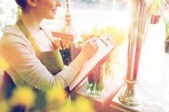 Zamyka up kobieta z schowkiem przy kwiatu sklepem Zdjęcia Royalty Free