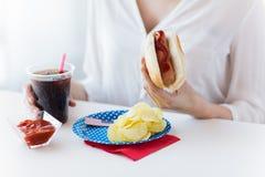 Zamyka up kobiety łasowania hot dog z koka-kolą zdjęcia royalty free