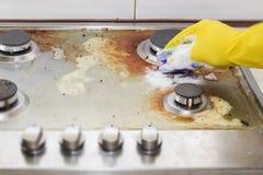 Zamyka up kobiety cleaning kuchenki kuchnia w domu Fotografia Stock