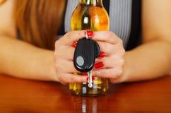 Zamyka up kobiety mienie z oba rękami botle piwa i samochodu klucze nad drewnianym stołem Zdjęcia Stock