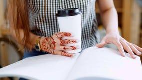 Zamyka up kobiety writing w jej czasopiśmie w ruchliwie sklep z kawą i obsiadanie zbiory wideo