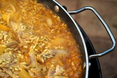 Zamyka up kurczaka paella kucharstwo w niecce z chrom rękojeścią obrazy royalty free