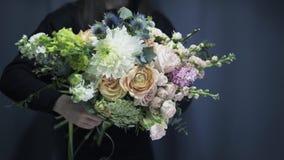 Zamyka up kwiatu sklepu pracownik trzyma wiązkę piękni kwiaty zbiory