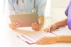 Zamyka up lekarki z pastylka komputerem osobistym przy szpitalem Obraz Royalty Free