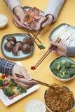 Zamyka up ludzie używa chopsticks z Chińskim jedzeniem fotografia royalty free