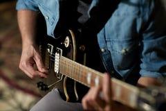 Zamyka up mężczyzna bawić się gitarę przy pracownianą próbą Obraz Royalty Free