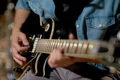 Zamyka up mężczyzna bawić się gitarę przy pracownianą próbą Fotografia Royalty Free