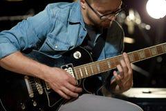 Zamyka up mężczyzna bawić się gitarę przy pracownianą próbą Obrazy Royalty Free