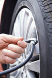 Zamyka Up mężczyzna pompowania Samochodowa opona Z Lotniczą Ciśnieniową linią Fotografia Stock