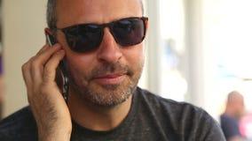 Zamyka Up mężczyzna używa telefon komórkowego w kawiarni zbiory wideo