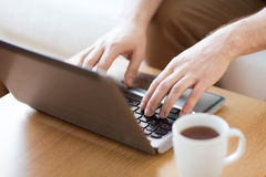 Zamyka up mężczyzna z laptopem i filiżanką w domu Zdjęcie Royalty Free