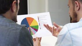 Zamyka up męscy partnery biznesowi egzamininuje drukowanego diagram zdjęcie royalty free