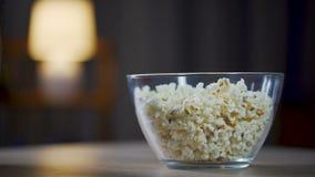 Zamyka up męski łasowanie popkorn od pucharu na stole, niezdrowy karmowy nałogowiec zbiory wideo