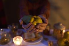 Zamyka up męskie ręki trzyma pigwy na ciemnym tle Obrazy Royalty Free