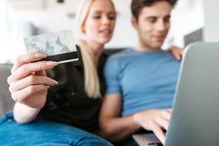 Zamyka up młoda kobieta trzyma kredytową kartę podczas gdy używać laptop z jej mężem Zdjęcie Stock