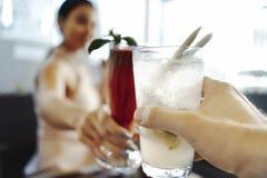 Zamyka up młodej atrakcyjnej kobiety clinking szkła smoothie i lemoniada przy uliczną kawiarnią zdjęcia royalty free