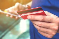 Zamyka up młody człowiek trzyma kredytową kartę i używa mądrze telefon Zdjęcia Stock