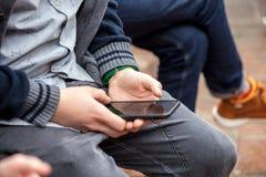 Zamyka up młody człowiek używa smartphone, ostrość na rękach trzyma telefon zdjęcie royalty free