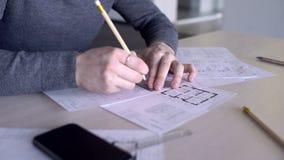 Zamyka up młody męski arcitect który pracuje na budynku projekcie w jego biurze, zdjęcie wideo