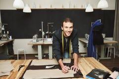 Zamyka up młody rozochocony atrakcyjny męski odzieżowy projektant z elegancką fryzurą w kostiumu pracuje na nowej kolekci wewnątr Fotografia Stock