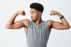 Zamyka up młody sportowy przystojny ciemnoskóry mężczyzna z afro fryzurą w sporty popielaty koszulowym patrzejący jego mięśnie Obraz Royalty Free
