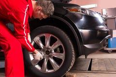 Zamyka up męska auto mechanika pozycja blisko czarnego s i sedanu Zdjęcia Royalty Free
