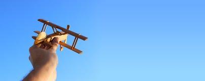 zamyka up man& x27; s ręki mienia zabawki samolot przeciw niebieskiemu niebu Fotografia Stock