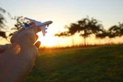 zamyka up man& x27; s ręki mienia zabawki samolot przeciw zmierzchu niebu Obrazy Royalty Free