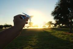 zamyka up man& x27; s ręki mienia zabawki samolot przeciw zmierzchu niebu Fotografia Stock