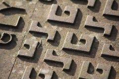 Zamyka up manhole pokrywa z ` G ` i ` S ` wzorem Obrazy Stock