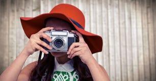 Zamyka up millennial kobieta z kamerą w lato kapeluszu przeciw rozmytemu drewnianemu panelowi obrazy royalty free