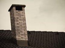Zamyka up na ceglanym kominie na dachu odizolowywającym w niebie Fotografia Stock