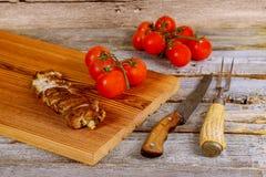 Zamyka up na drewnianej desce z piec na grillu wieprzowina stkiem obok czereśniowych pomidorów na drewnianym stole Zdjęcie Royalty Free