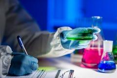Zamyka up naukowa writing wyniki testu w lab Obrazy Royalty Free
