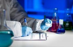 Zamyka up naukowa writing wyniki testu w lab Fotografia Stock