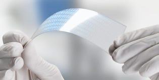 Zamyka up naukowy trzyma strój jednoczęściowy przejrzysty graphene zastosowanie z binarnymi liczbami. Obraz Royalty Free